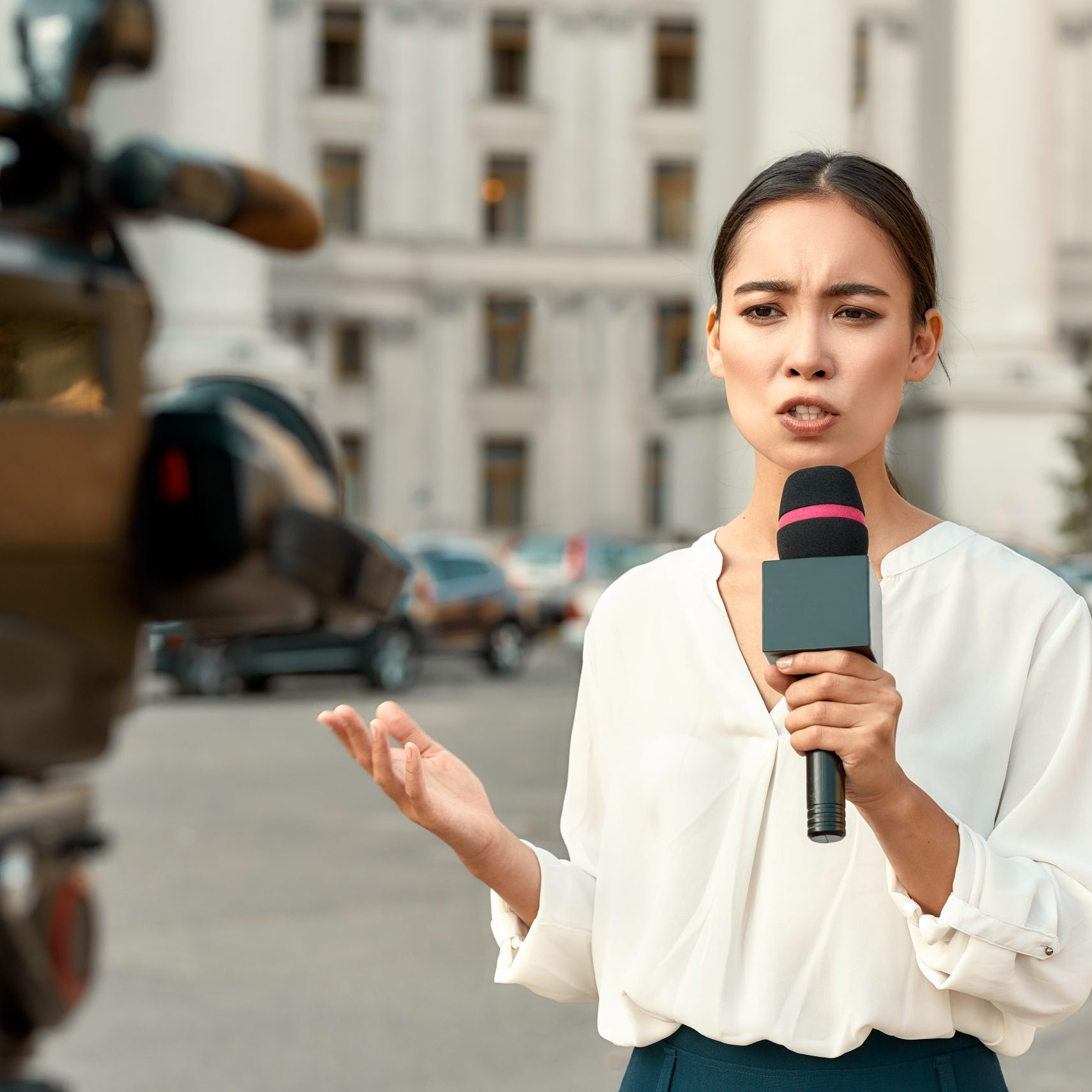 Cropped portrait of professional female reporter at work. Young woman standing on the street with a microphone in hand and smiling at camera. Horizontal shot. Selective focus on woman